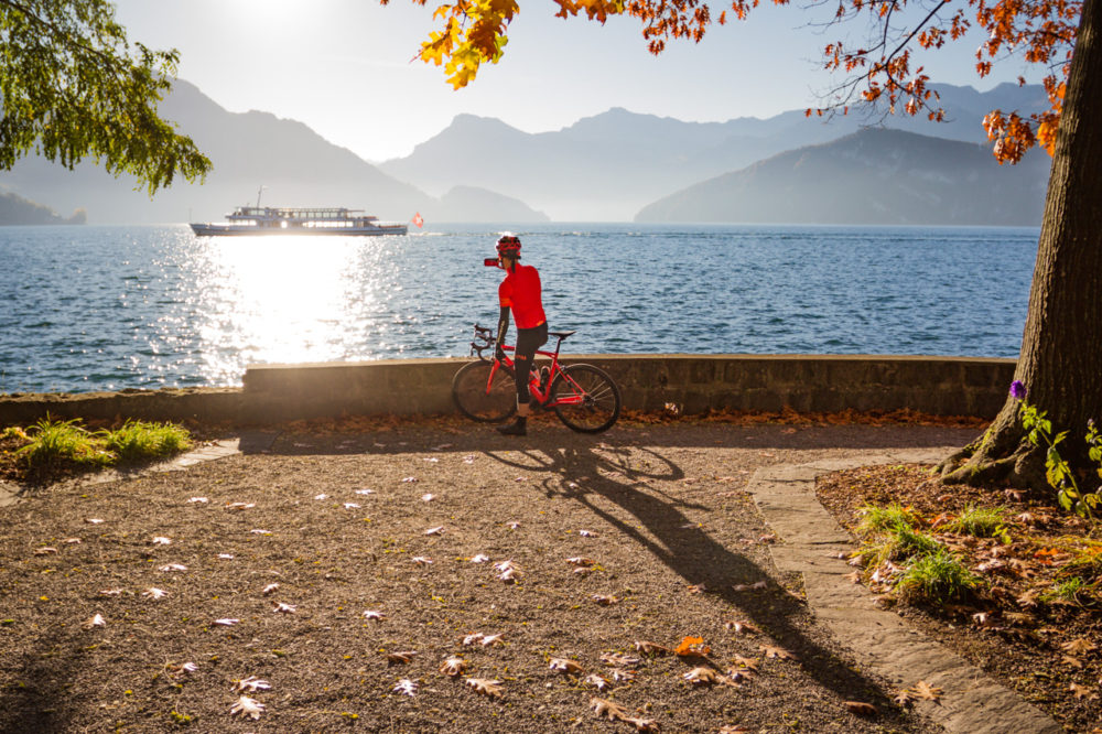 One male cyclist taking a photo on the shore of Lake Lucerne in Kanton Luzern, Switzerland